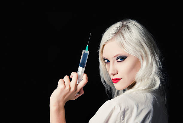 Beautiful young girl in the image of nurse with syringe stock photo