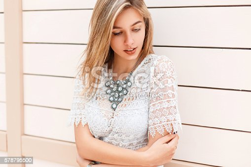 578791454istockphoto Beautiful young girl in white lacy blouse near wooden wall 578795500