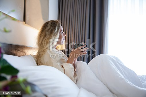 Beautiful young girl is drinking morning coffee in bed