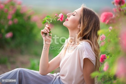 Portrait of beautiful pretty woman with makeup is walking near roses in blossom pink garden