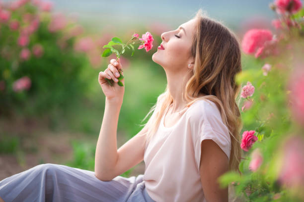 beautiful young girl is wearing casual clothes having rest in a garden with pink blossom roses - scented stock photos and pictures