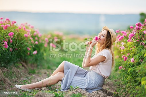 Beautiful pretty woman is sitting near roses in a garden. The concept of perfume advertising.