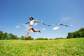 Cute young girl long jump waving with colorful ribbon over field and sky background