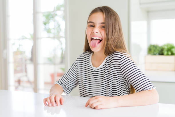 Beautiful young girl kid wearing stripes t-shirt sticking tongue out happy with funny expression. Emotion concept. Beautiful young girl kid wearing stripes t-shirt sticking tongue out happy with funny expression. Emotion concept. tongue stock pictures, royalty-free photos & images