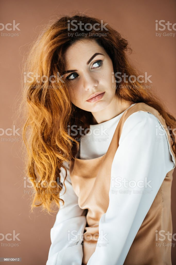 Beautiful young girl looking away isolated on brown background royalty-free stock photo