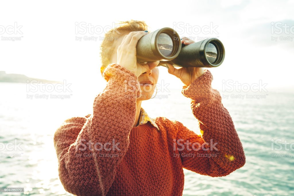 Beautiful Young Girl Looking Through Binoculars At The Sea On A Bright Sunny Day. Wanderlust Journey Concept stock photo