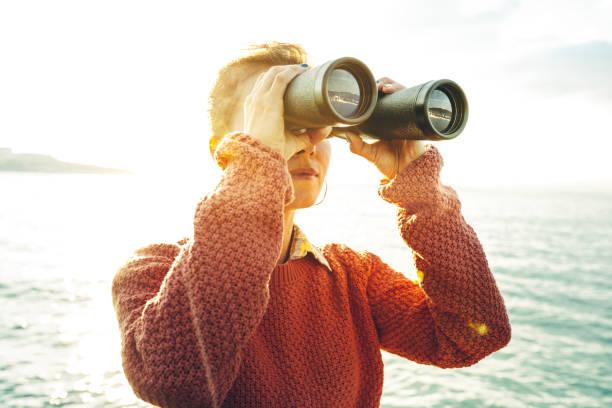 Belle jeune fille à la recherche à travers des jumelles à la mer sur une belle journée ensoleillée. Concept de voyage Wanderlust - Photo