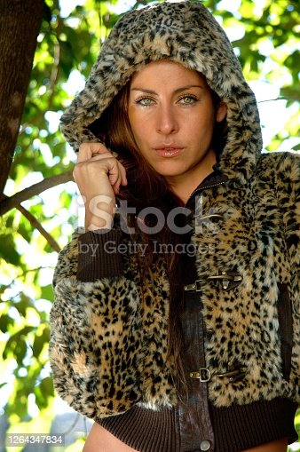 Gorgeous young girl on the tree with a jacket