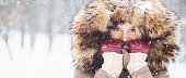 istock Beautiful young girl outdoors in the snow wearing hood 614648796