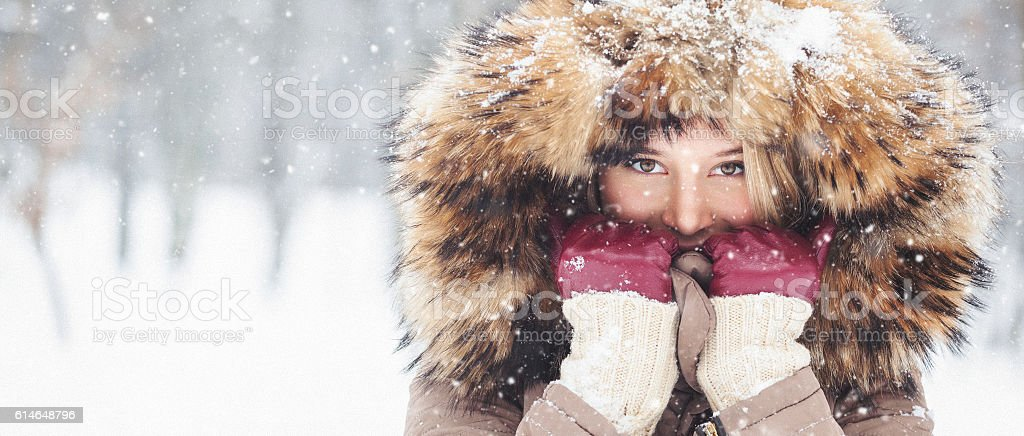 Beautiful young girl outdoors in the snow wearing hood stock photo