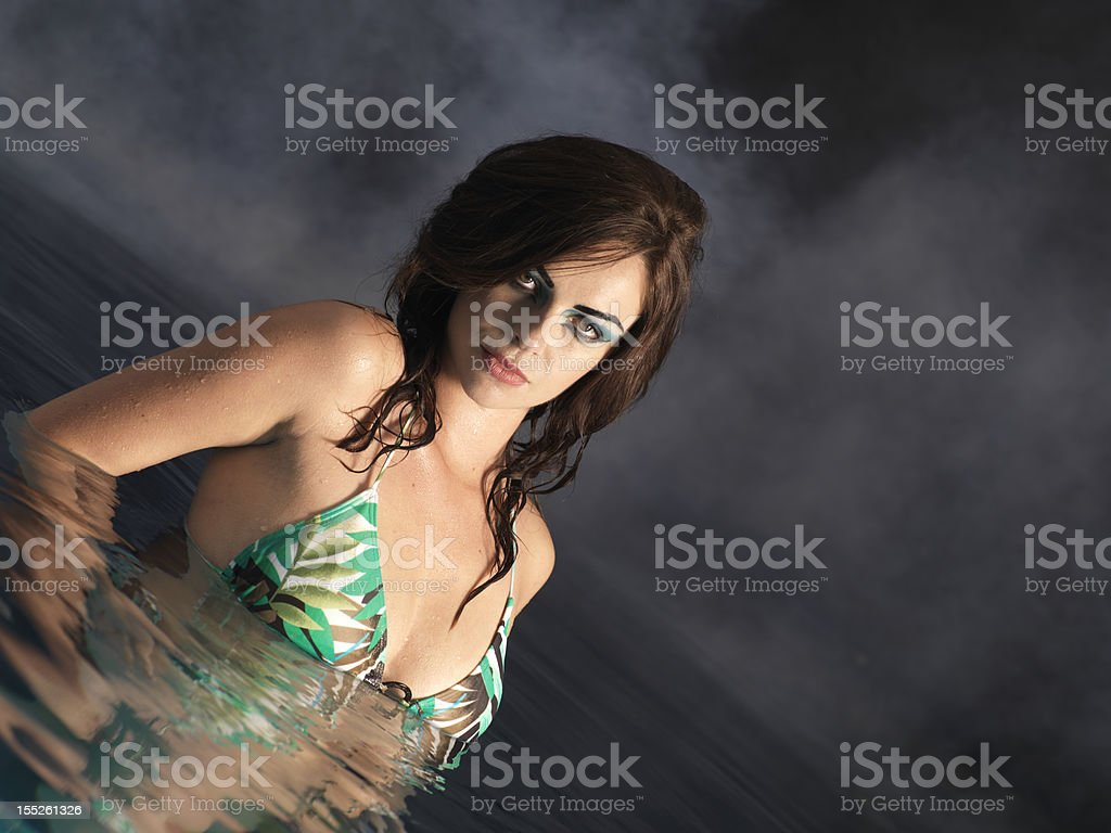 Beautiful young girl posing in the pool royalty-free stock photo