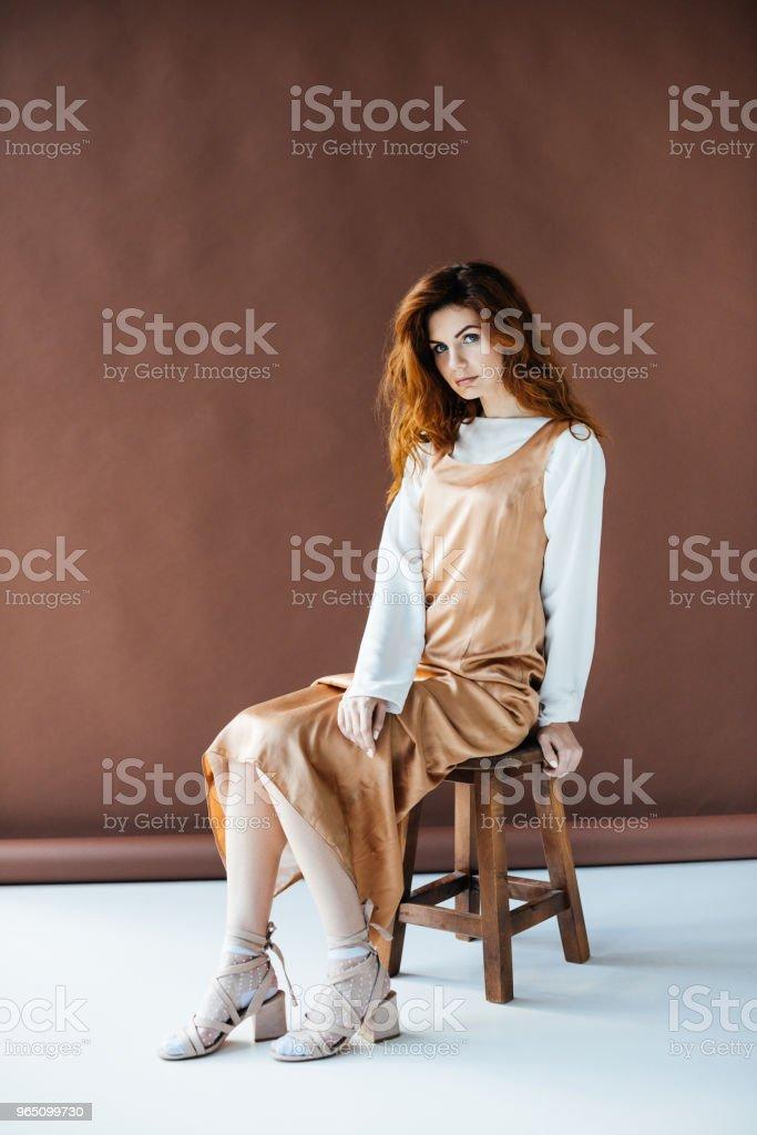 Beautiful young girl posing on wooden chair zbiór zdjęć royalty-free