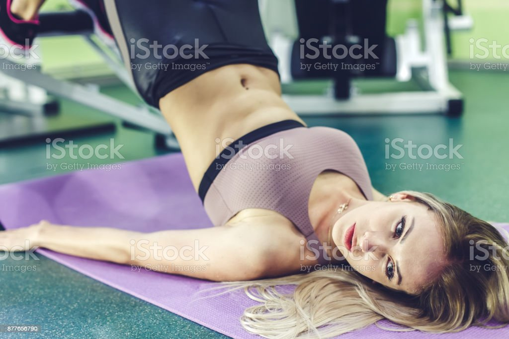 Beautiful young girl pumping abdominal muscles  in a GYM. Helthy lifestyle concept. stock photo