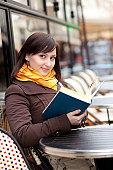 istock Beautiful young girl reading a book in Parisian street cafe 155743416