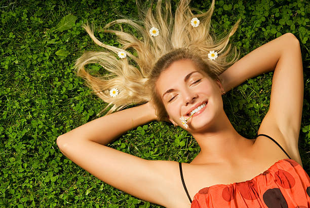 Beautiful young girl relaxing on a meadow stock photo