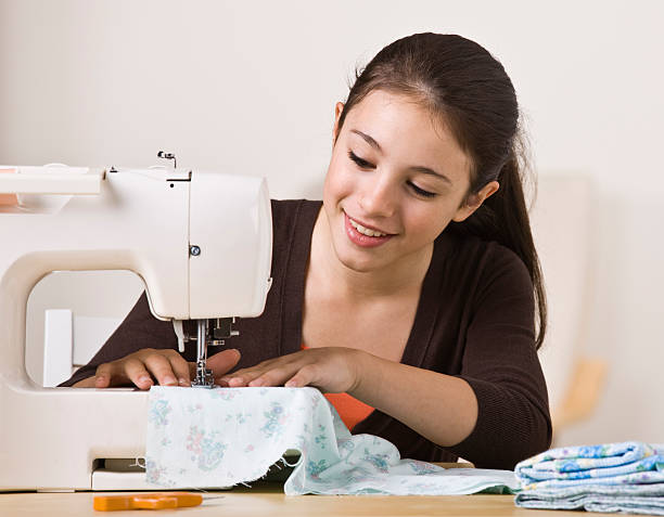Beautiful Young Girl Sewing A beautiful, smiling young girl sewing on a sewing machine.  Horizontally framed shot.   stitching stock pictures, royalty-free photos & images