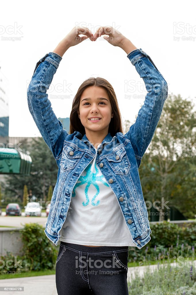 Beautiful young girl showing a heart with her hands stock photo