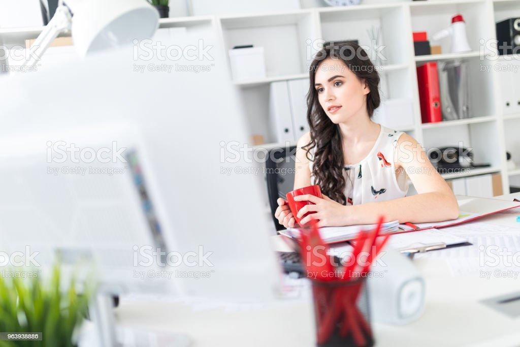 美しい少女のオフィスの机で座っているコンピューターの画面を見て、手に赤いマグカップを保持します。 - 1人のロイヤリティフリーストックフォト
