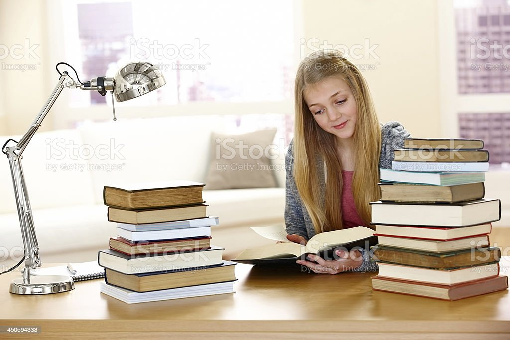 Beautiful young girl sitting at desk reading book royalty-free stock photo