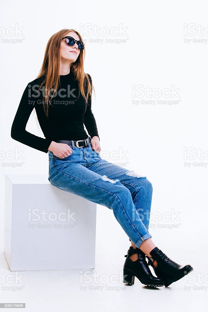 Beautiful young girl sitting on a white cube stock photo