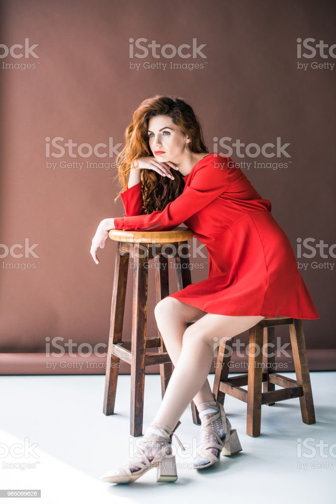 Beautiful young girl sitting on chair by tall stool zbiór zdjęć royalty-free