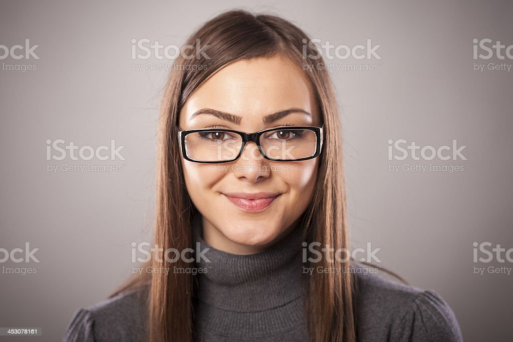 Beautiful young girl smiling on gray background stock photo