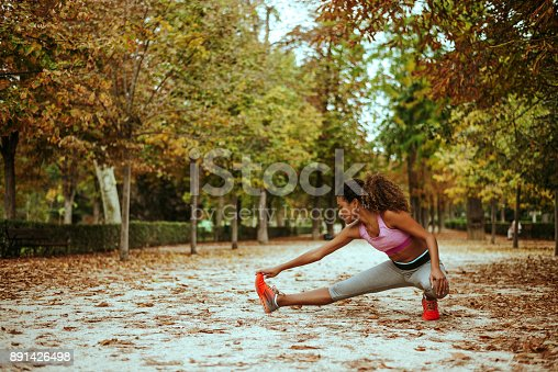 istock Beautiful young girl stretching legs before training in park. 891426498