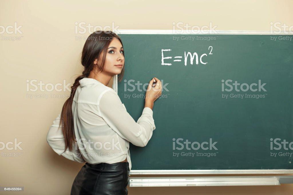 Beautiful young girl teacher writing formula on the blackboard. stock photo