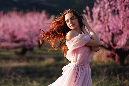 Beautiful young girl under the flowering pink tree