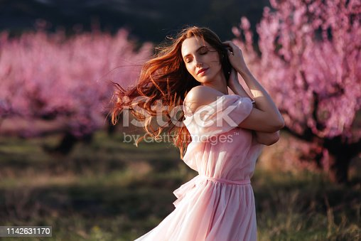 Beautiful young girl under the flowering pink spring tree