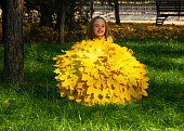 Beautiful young girl walks in the park with an umbrella from autumn yellow leaves. Autumn time, September, October, November. Craft from the leaves. Fall foliage in the city
