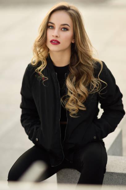 schöne junge mädchen tragen schwarze jacke sitzen auf der straße. - winterjacke lang damen stock-fotos und bilder
