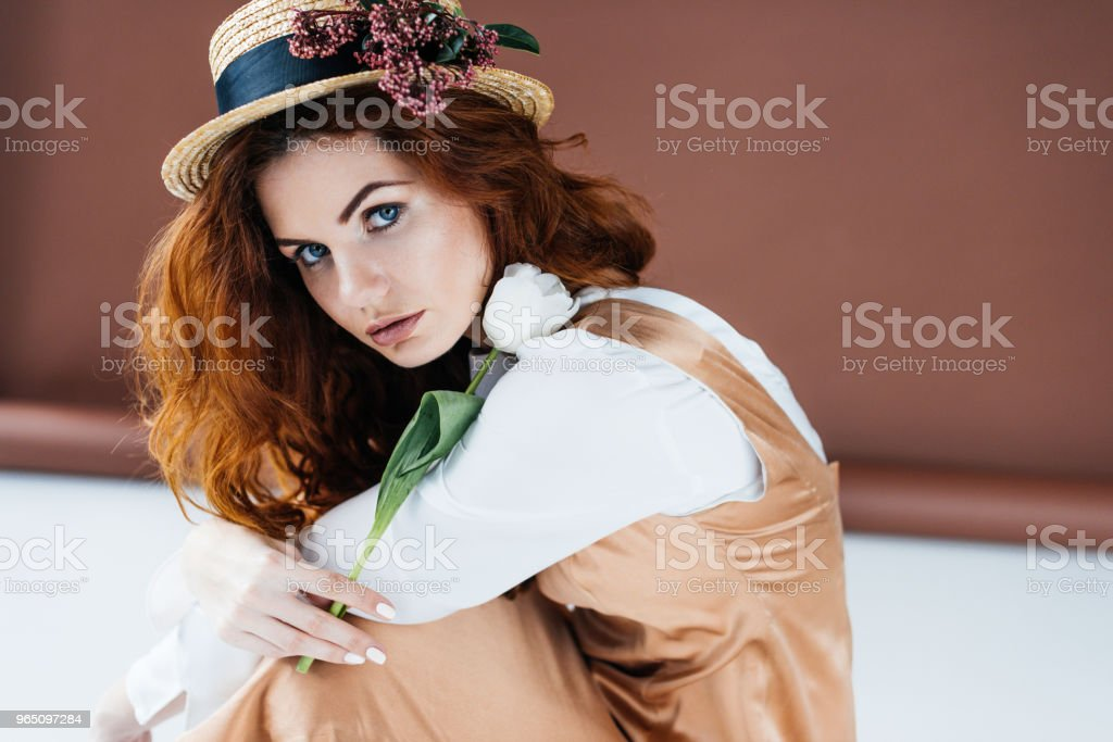 Beautiful young girl wearing straw hat with flowers and holding tulip royalty-free stock photo