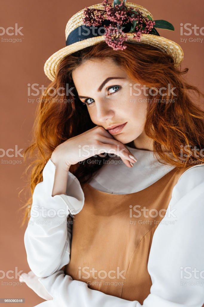 Beautiful young girl wearing straw hat with flowers isolated on brown background royalty-free stock photo