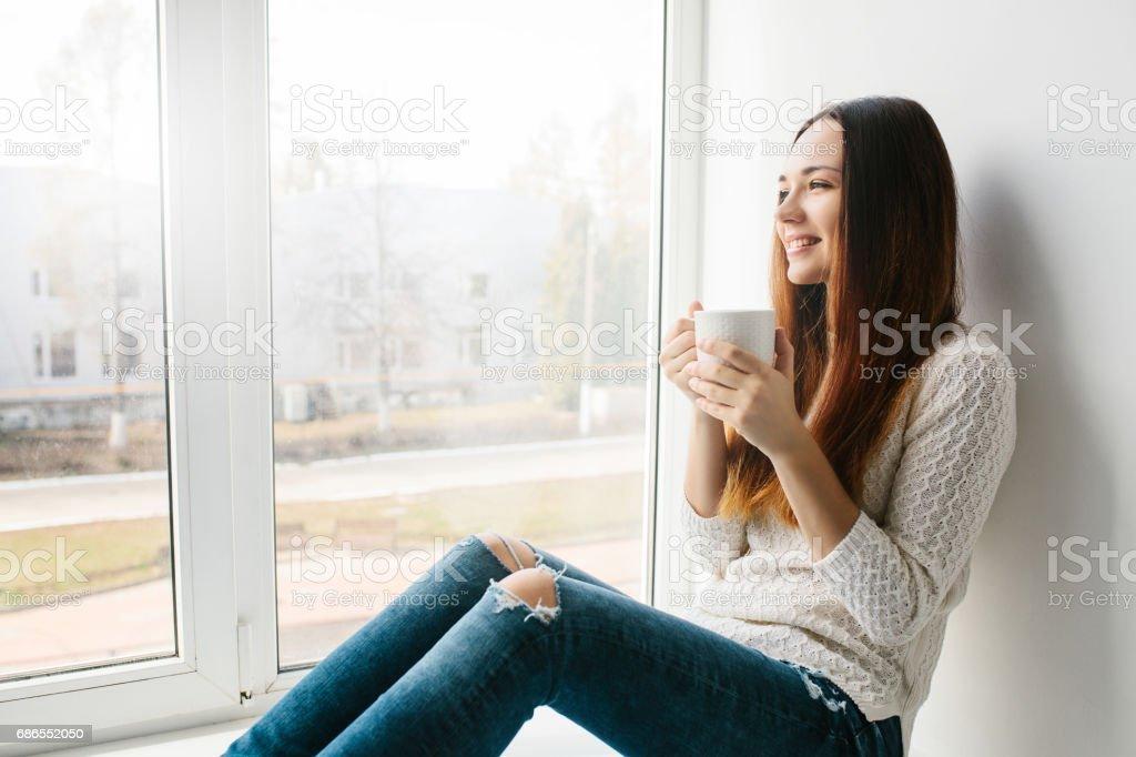 紅茶のカップを持つ美しい少女は窓際に座っています。 ロイヤリティフリーストックフォト
