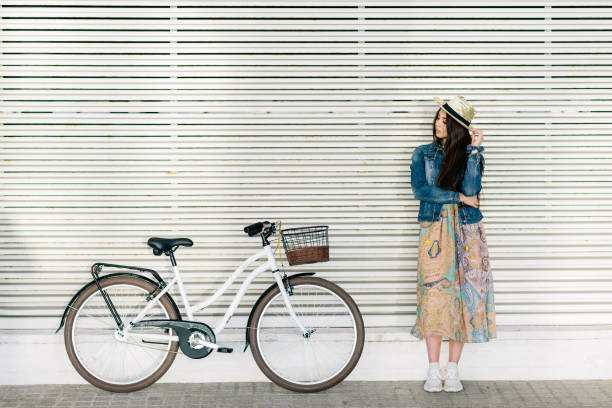 Beautiful young girl with a pretty smile waiting for a friend to take a ride with her bike