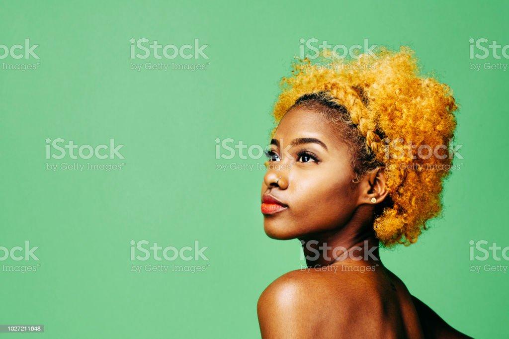 Hermosa joven con pelo rizado blanqueado y hombro desnudo mirando hacia arriba - foto de stock