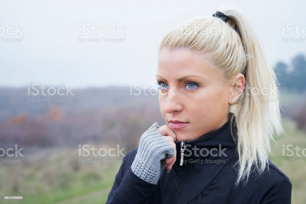 Beautiful young girl with bleu eyes in sportwear posing in nature stock photo