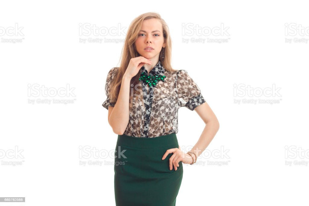 beautiful young girl with blond hair and attire keeps one hand near the face and the other on the side and looks straight royalty-free stock photo
