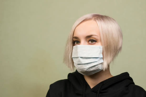 Beautiful young girl with blond hair in a black hoodie in a sterile protective medical mask stock photo