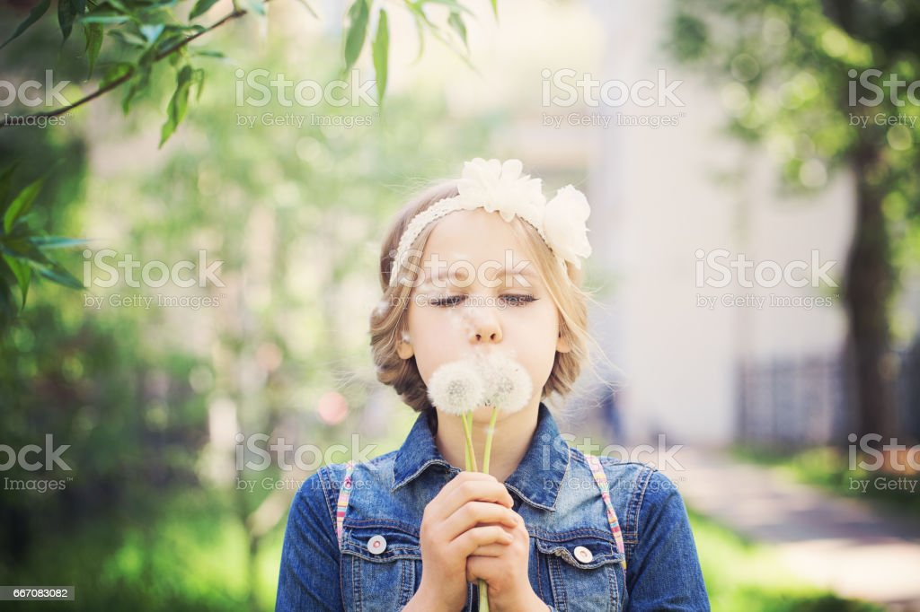 Beautiful Young Girl with Blonde Hair. Prom Hairstyle and Dandelion Flowers stock photo