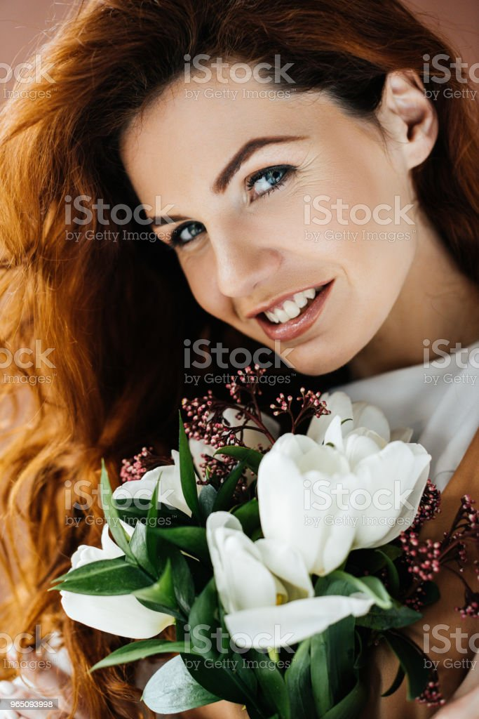 Beautiful young girl with bouquet of flowers isolated on brown background royalty-free stock photo