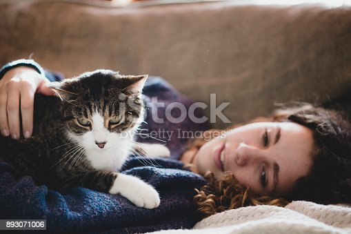 istock Beautiful young girl with her cat 893071006