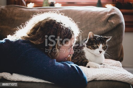 istock Beautiful young girl with her cat 893071072