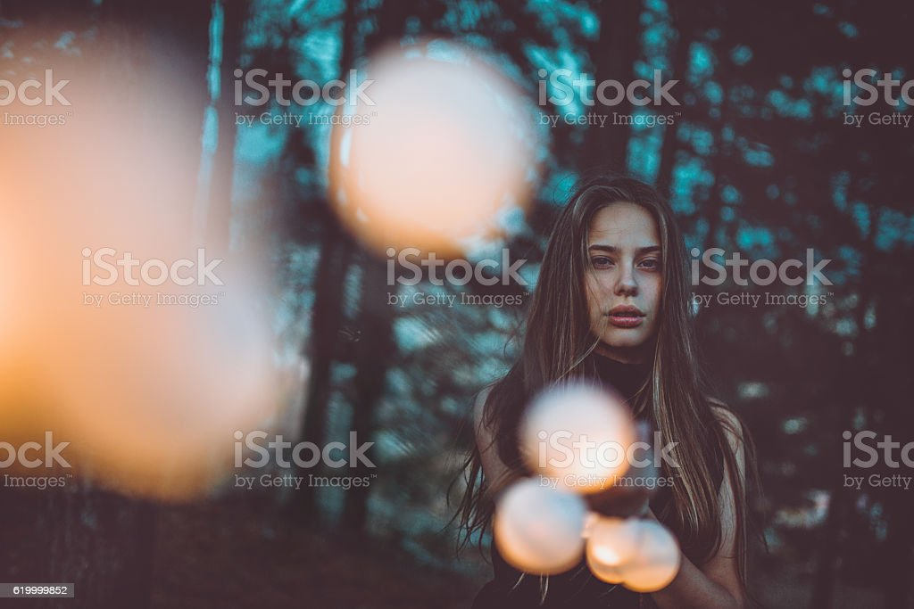 Beautiful Young Girl with Light bulbs at Night in Forest stock photo