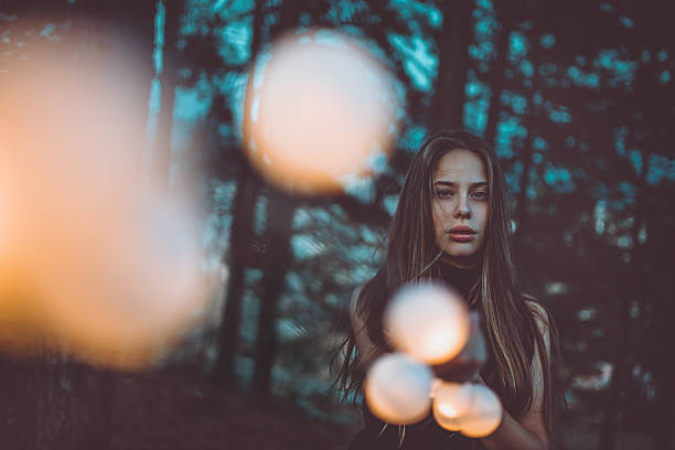 beautiful young girl with light bulbs at night in forest - cérémonie photos et images de collection