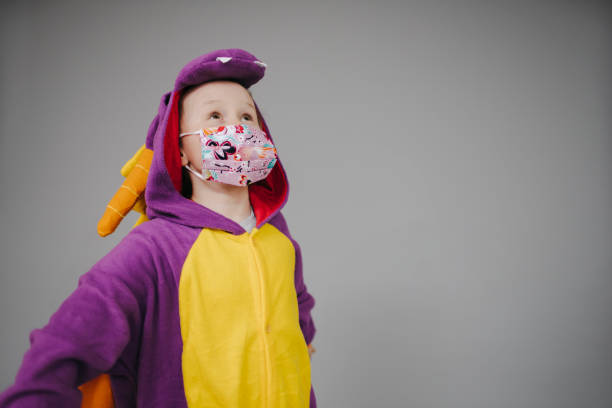 beautiful young girl with mask and dragon costume stock photo