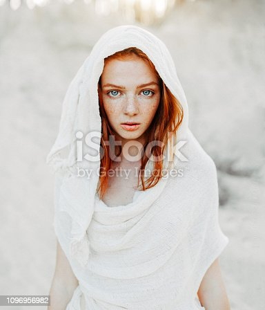 A beautiful young girl with red hair and freckles looks intently at the camera. Woman in the hood and clothes for the desert. Concept.
