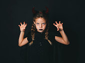 beautiful young girl with red halloween horns and cape in front of black background