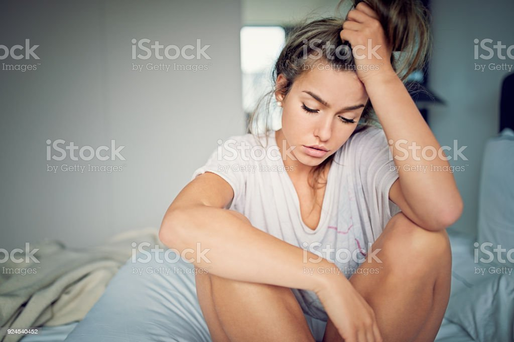 Beautiful young girl with relationship difficulties standing sad in the bed stock photo